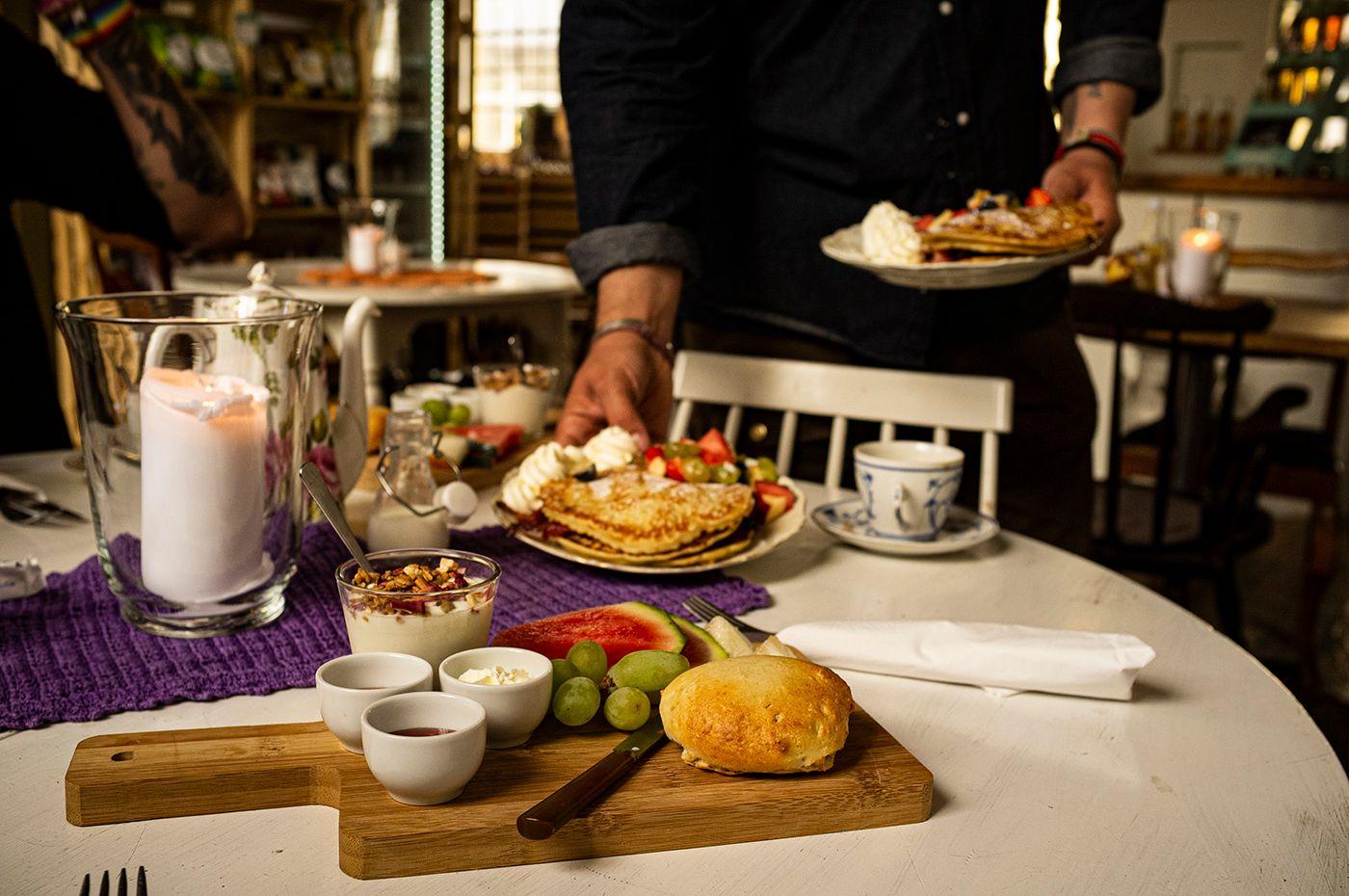 """Äppelpankaka med grädde och bacon påväg att serveras till bordet belamrat med scones och yoggi och annat gott som ingår i Kullamust """"frulle"""""""